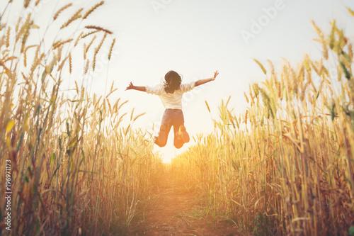 Fototapeta Back view of jumping girl in the barley farm.Freedom concept. obraz