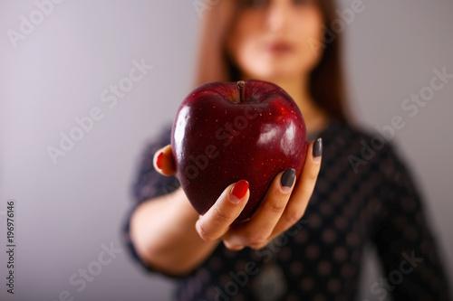 Fotografía A red ripe apple in a beautiful female hand