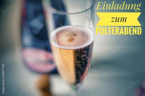 Valokuva  Champagnerglas mit edlem Champagner und Aufschrift in gelb auf deutsch Einladung