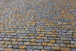 Texture of the stone pavement of cobblestones grey and yellow