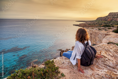 Spoed Foto op Canvas Cyprus A stylish young woman traveler watches a beautiful sunset on the rocks on the beach, Cyprus, Cape Greco, a popular destination for summer travel in Europe
