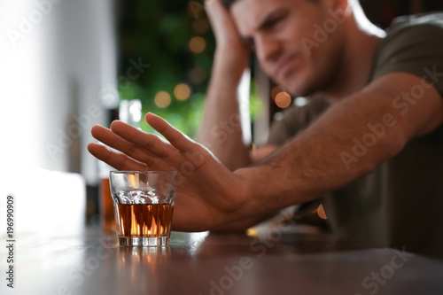 Man refusing to drink alcohol in bar, closeup