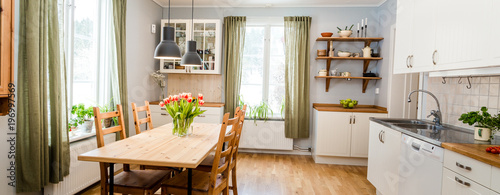 Banner Of Cozy Kitchen Interior With Green Curtains And Red Tulips