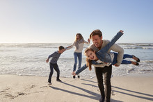 Parents With Children Having Fun On Winter Beach Together
