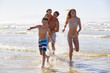 Family On Summer Beach Vacation Run Out Of Sea Towards Camera