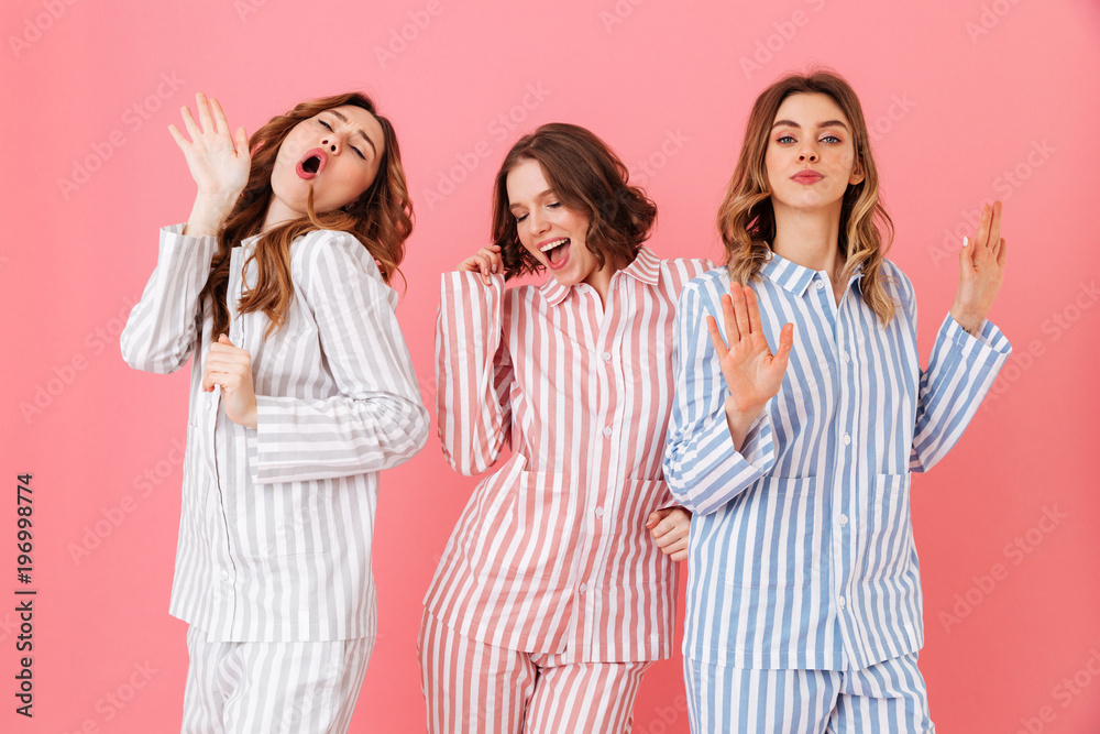 Fototapety, obrazy: Portrait of three beautiful young girls 20s wearing colorful striped pyjamas having fun during sleepover, isolated over pink background