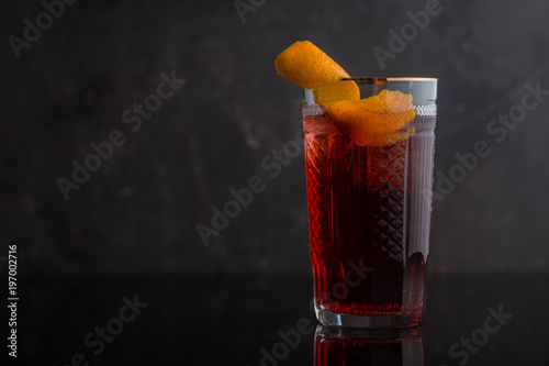 Close up of negroni cocktail garnished with citrus peel