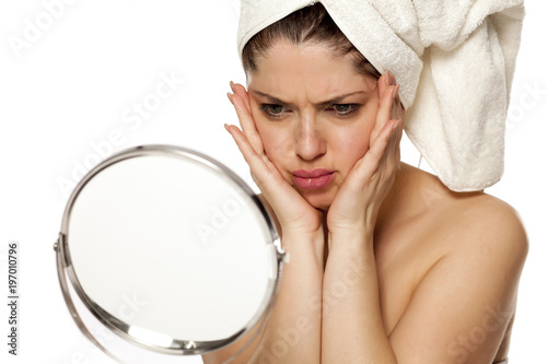Young beautiful woman with towel on hr head on white background tighten her face skin