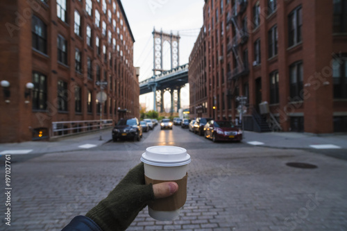 Man holding coffee cup in New York City Wallpaper Mural