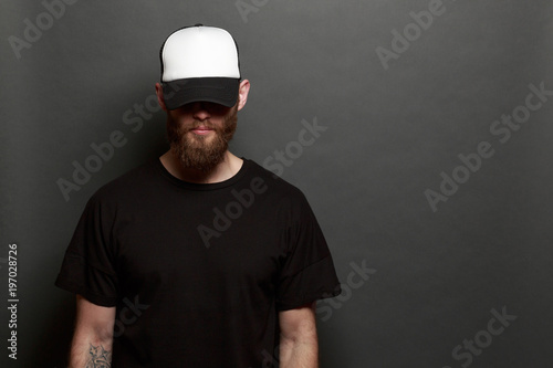 d7dfd7c0 Hipster man walking wearing black jeans, t-shirt and a white baseball cap