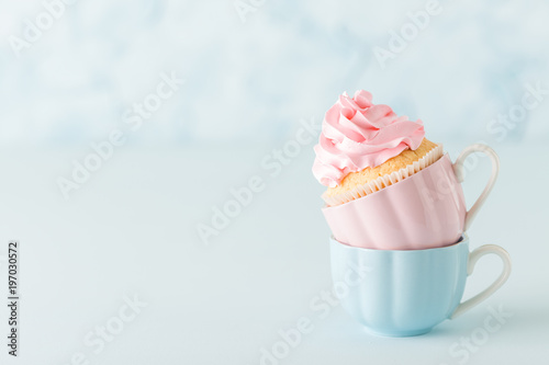 Photo  Cupcake with pink buttercream decoration in two cups on blue pastel background