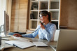 canvas print picture - Businesswoman in her office.She sitting at the desk and talking on the phone.