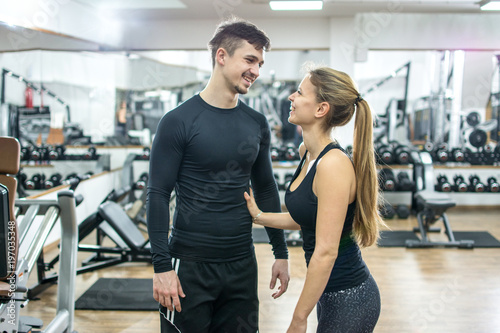Beautiful young woman and man flirting in gym Fototapet