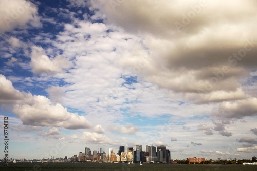 Manhattan under the cloudy sky with the long distance view from ferry in New York