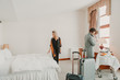 Family with suitcases in hotel room