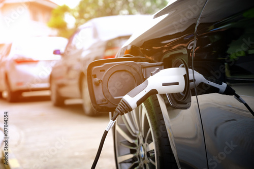 Fotomural Charging modern electric car battery on the street which are the future of the Automobile, Close up of power supply plugged into an electric car being charged for hybrid
