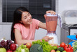 woman making smoothies with blender in kitchen