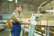 Side view portrait of mature man working in industrial workshop choosing material for cutting, wood and glass sheets, copy space