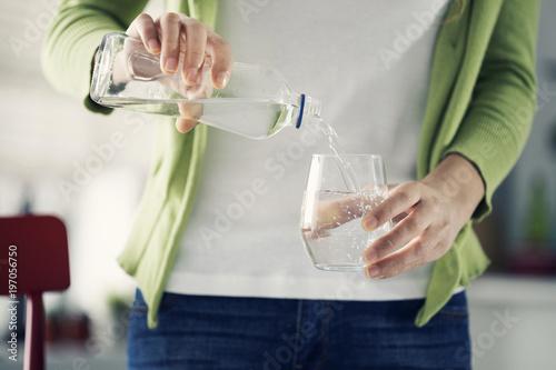 Zdjęcie XXL Kobieta wlewając wodę z butelki do szkła
