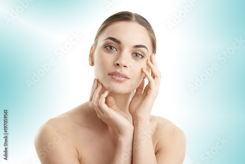 Fototapeta Healthy glowing skin. Portrait of beautiful young woman with toothy smile and radiant skin posing at isolated white background.  obraz na płótnie