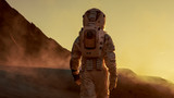 Fototapeta Fototapety kosmos - Shot of Astronaut Confidently Walking on Mars. Red Planet Covered in Gas and Smoke. Humans Overcoming Difficulties. Big Moment for the Human Race.