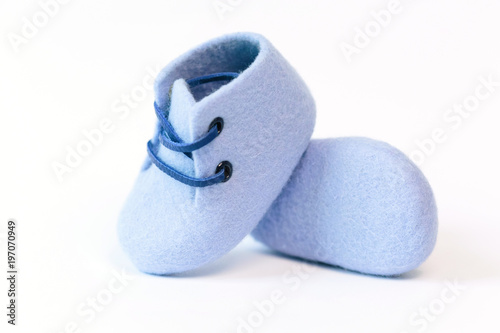 Blue handmade baby shoes made of merino wool on a white background.