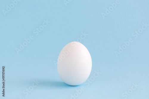 Foto White egg isolated on pale blue background.