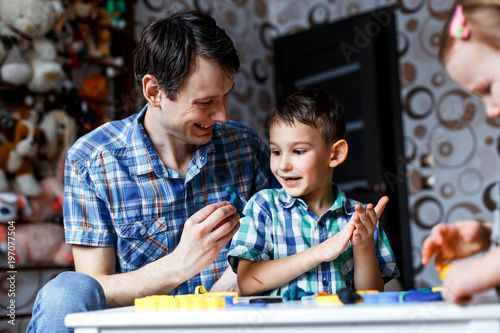 Papiers peints Attraction parc Picture of a father and a son playing with color play dough and cutters. Having fun with colorful modeling clay. Creative kids molding at home. Children play with plasticine or dough.
