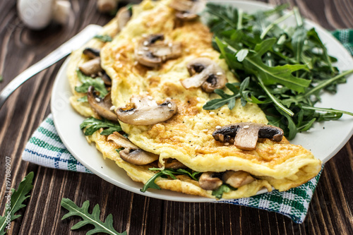 Fotografía  Omelette with mushrooms and arugula on a wooden background