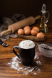 mug flour, eggs, rolling pin, olive oil in a jar on a wooden background