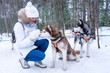 Cute girl playing with many husky in the forest during winter.