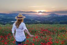 Woman Standing In Poppy Field And Enjoying A Sunset