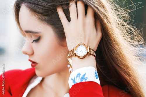 Close up outdoor photo of stylish golden wrist watch on the woman`s hand. Selective focus, face out of focus. Fashion details