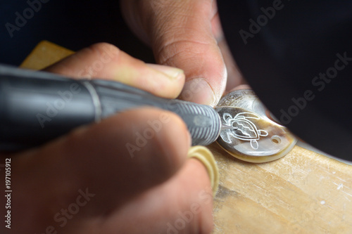 Cook Islander Maori engraves sea turtle on a Black Pearl shell Rarotonga Cook Islands