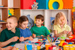 Plasticine modeling clay in children class. Teacher teaches kids together play dough and mold from plasticine in kindergarten or preschool. Group of four people.