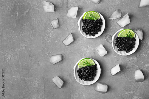 Plates with black caviar and ice cubes on grey background