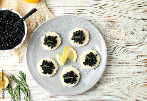 Sandwiches with black caviar and lemon slice on plate