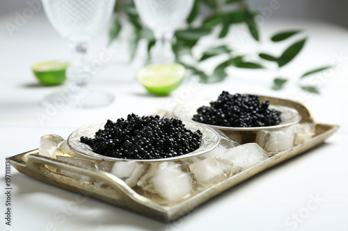Plates with black caviar served with ice cubes on table