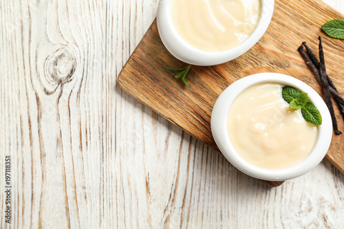 Vanilla pudding, sticks and fresh mint on wooden board Wallpaper Mural