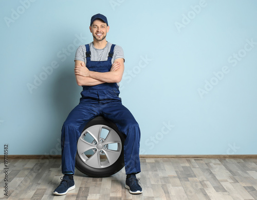 Fotografía  Male mechanic with car tire on color wall background