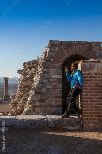 Fotografie, Obraz  Man in baseball cap NYC is sitting under the arc of The Gate of Augustus in Ephesus was built to honor the Emperor Augustus and his family