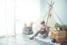Young Asian Boy Playing Ukulele In Front Of Tent At Home