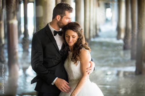 Valokuvatapetti Beautiful romantic portrait of newlywed couple by water underneath gorgeous ocea