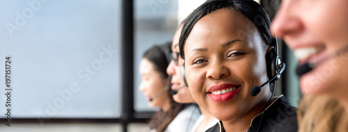 Friendly black woman wearing microphone headset working in call center Canvas Print
