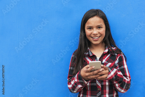 Fotografie, Obraz  Portrait of cute latino girl using the mobile in the street.