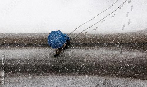 Pedone con ombrello sulla strada con la neve Canvas Print