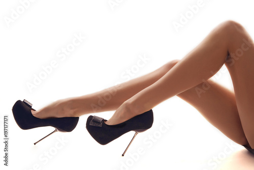 Foto  Beautiful woman legs wearing a high stiletto heels isolated on a white backgroun