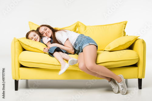 Happy mother and daughter on sofa isolated on white Fototapeta