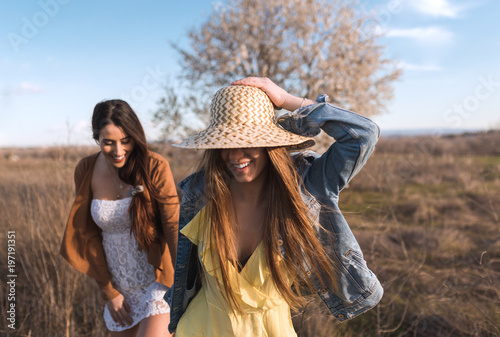 Cheerful women walking and playing happy in field