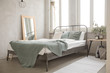 Bed with green coverlet stands in bright bedroom with large French windows mirror and small bedside lamp with a plant and alarm clock. Well decorated bedroom in soft lights